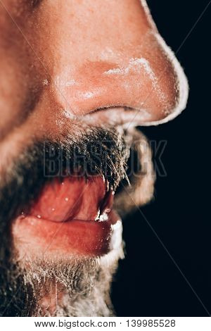Man feeling good after sniffing cocaine and licking cocain of his mustache.