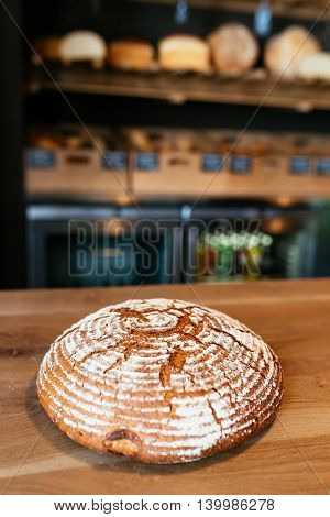 Blurry pose of composition of fresh baked bread on wooden table with focus on the bread
