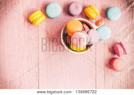 Vintage colorful macarons on pink wooden background.