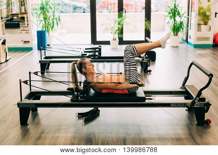 Ambitious woman working out on a pilates reformer