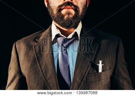 Drug addict in nice suit having a syringe in his pocket
