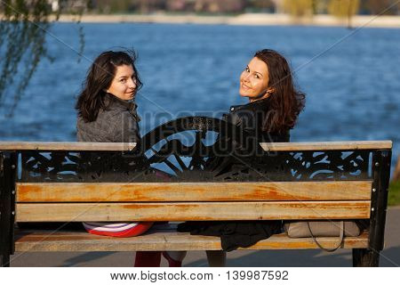 Closeup of two smiling woman sitting on a bench near a lake and looking behind to the camera