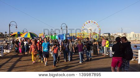 Los Angeles CA USA - July 6 2013: Groups of tourists visiting Pacific Park on Santa Monica peer. Ferris Wheel in the background.