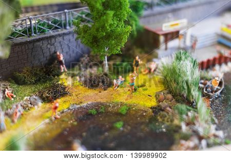 City In Miniature. River Beach With Miniature People.