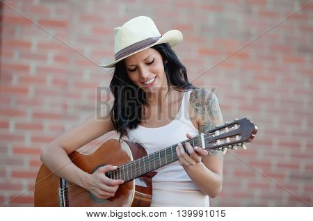 Brunette pretty woman playing a clasic guitar
