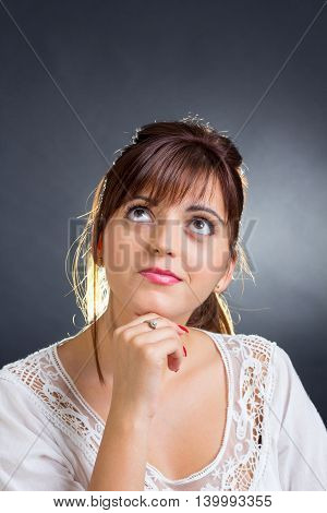 Portrait of a young woman thinking and looking up