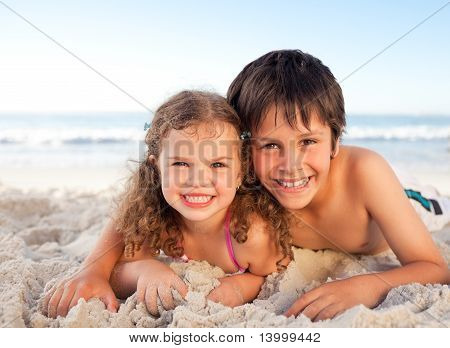 Little Boy And His Sister Lying Down On The Beach