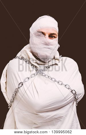 Bandaged patient in straitjacket and chains sepia version