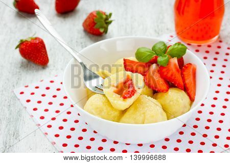 Lazy dumplings with cottage cheese and fresh strawberries in the filling selective focus poster