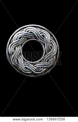 Close up of a silver celtic type symbol
