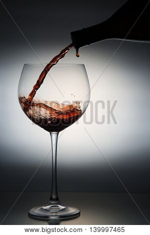 backlit portrait of red wine in tasting glass
