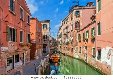Old colorful houses and narrow canal between them under blue sky in Venice, Italy.