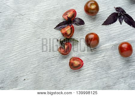 Tomatoes with basil on wooden table background. Food composition. Top view.