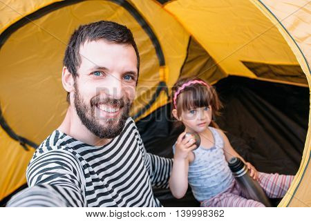 Dad with baby in tent taking selfie, family trip to forest, rest in camping