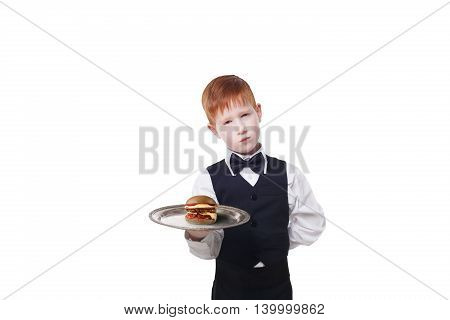 Little sad and tire waiter stands with tray serving hamburger. Redhead child boy in suit plays hardworking restaurant servant, gives burger isolated at white background