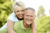 Mature couple having fun in countryside poster