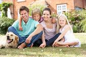 Family Sitting In Garden Together poster
