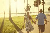 Middle aged couple walking together holding hands along the beach boardwalk. Abstract image of Building relationships and marital bonds. Early evening sunset and warm summer tone poster