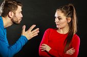 Husband apologizing upset angry wife. Man asking woman for forgivness. Boyfriend trying to convince girlfriend. Conflicted couple in studio on black. Relationship problem. poster