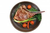 meat food : grilled beef spare rib on dark dish with thyme pepper and tomato isolated over white background poster