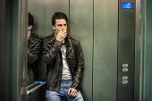 Scared young man desperate in stuck elevator screaming, looking very upset poster