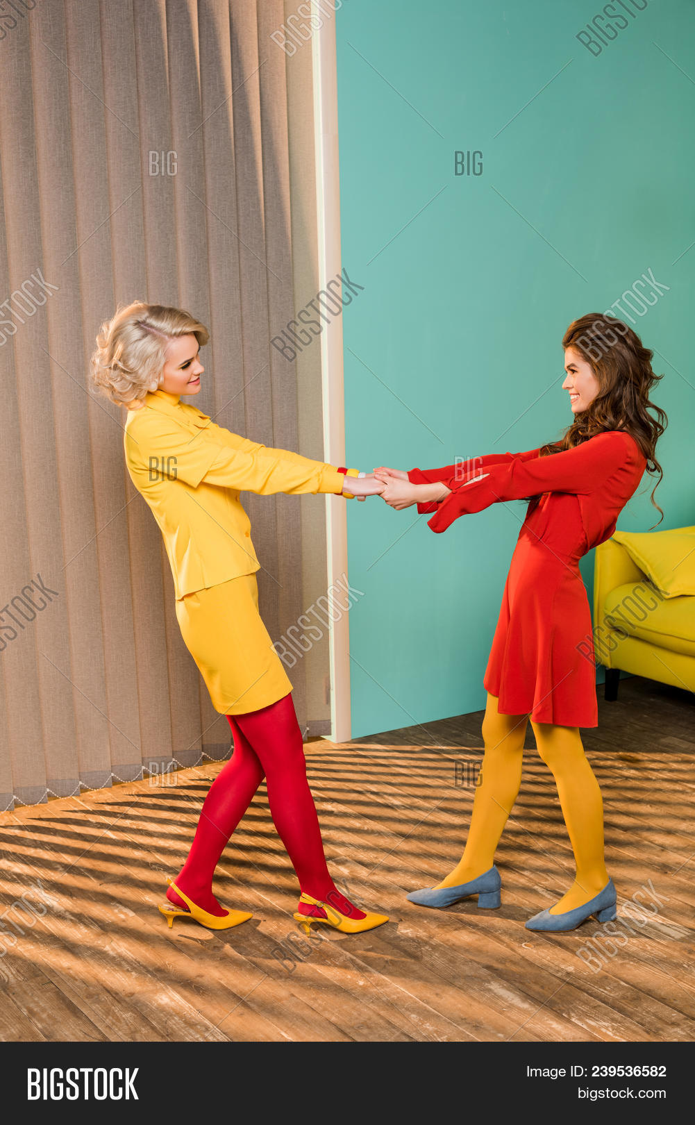 Side view of pretty smiling women in retro clothes holding hands at colorful apartment doll