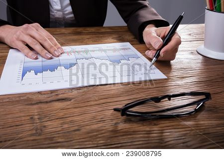 Close-up Of A Businessperson Analyzing Graph On Wooden Desk
