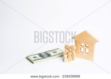 A Young Family Stands Near A Wooden House And With A Bundle Of Money. The Concept Of A Strong Family