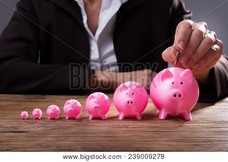 Businessperson's Hand Inserting Coin In Piggybank