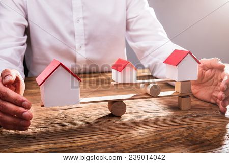 Businessperson's Hand Covering Balance Between House Models