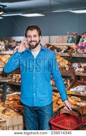 Portrait Of Smiling Shopper Talking On Smartphone In Grocery Shop
