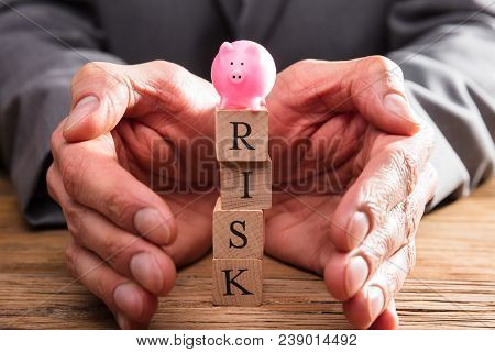 Businessperson Protecting Wooden Blocks With Risk Word