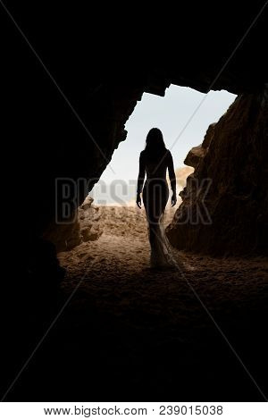 Beautiful And Sexy Woman Body Silhouette In Long Dress In A Cave