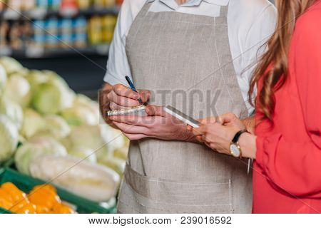 Partial View Of Shop Assistant With Notebook And Female Shopper In Supermarket