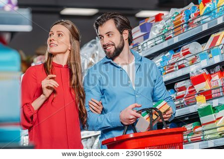 Portrait Of Smiling Couple With Shopping Basket Shopping Together In Supermarket
