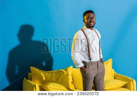 Stylish Young African American Man Standing With Hands In Pockets And Smiling At Camera