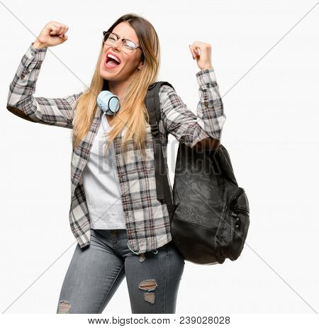Young student woman with headphones and backpack happy and excited celebrating victory expressing big success, power, energy and positive emotions. Celebrates new job joyful