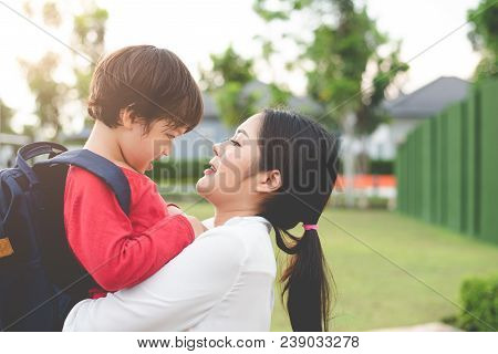 Mom Hug And Carry Her Son. Preparing To Send Her Children Back To School In Morning. Education And B
