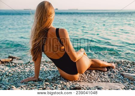 Beautiful Woman In Black Swimwear Relax On Sea With Warm Sunset Colors.