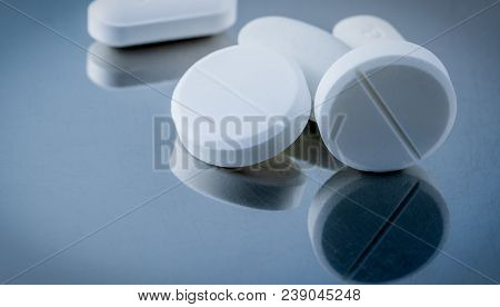 Macro Shot Of White Tablet Pills On Silver Background With Shadows. Antacids Pills For Relief Stomac