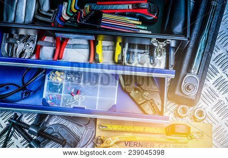 Top View Of Tools In Box On Checkered Plate Background In Workshop. Service Tools Set. Home Building