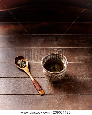 Green tea (sencha) in a traditional, japanese tea cup and sencha leaves on a wooden  tea spoon. Dark wooden background.  poster