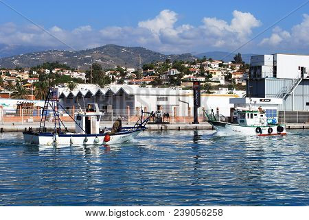 Caleta De Velez, Spain - October 27, 2008 - Traditional Fishing Boats Entering The Harbour With Buil