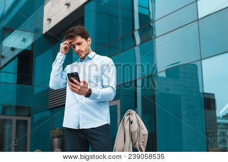 Hard Decision! Closeup Bottomup Picture Of The Young Intelligent Entrepreneur Using His Smartphone A