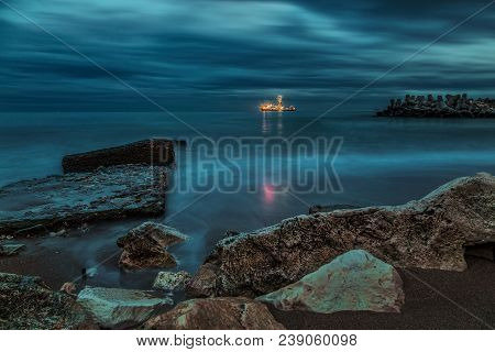 The Night Shore Of The Sea With The Ship In The Distance. Low Clouds, Rocks On The Shore.
