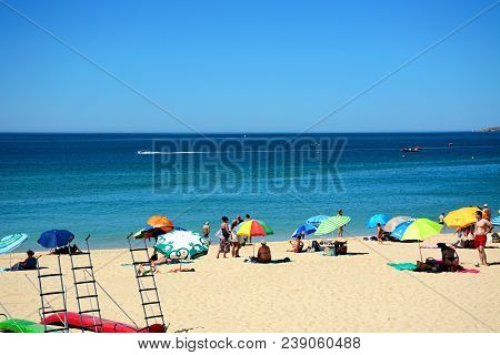 Portimao, Portugal - June 7, 2017 - Tourists Relaxing On The Beach With Views Across The Ocean, Prai