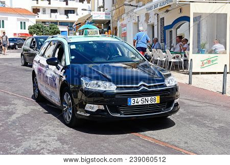 Albufeira, Portugal - June 8, 2017 - Portuguese Taxi With Tourist Cafes And Shops To The Rear, Albuf