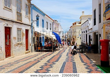 Lagos, Portugal - June 9, 2017 - Pavement Cafes And Shops Along The R 25 De Abril Shopping Street In