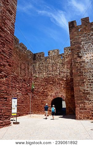 Silves, Portugal - June 10, 2017 - View Of The Medieval Castle Entrance With A Couple Of Tourists In
