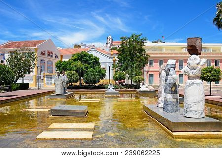 Silves, Portugal - June 10, 2017 - Statues In An Ornamental Pool In The Praca Al Mutamid With The Ca